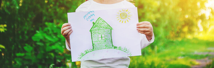 Drawing of a green house in the hands of a child. Selective focus.  Wall mural