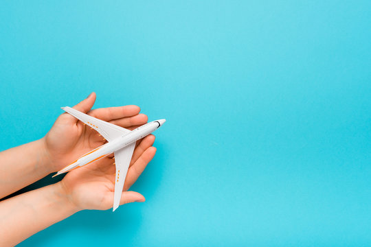 Hand carefully holding model plane. Airplane on blue color background. Security concept.