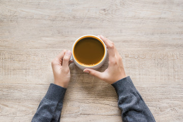 Female hand holding cup of coffee on wood texture background.