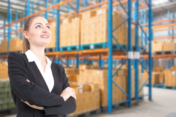 Businesswoman standing with attractive smile at warehouse background.