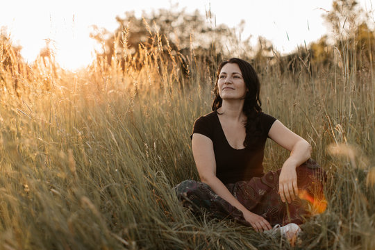 A portrait of a cheerful woman sitting cross legged in tall grass and enjoying sunset. A happy woman resting in the nature.