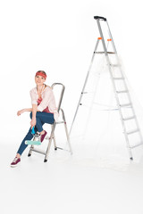 woman in headband sitting on small ladder near big ladder isolated on white background