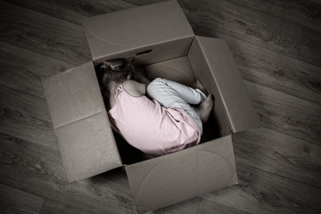 A sad little child lies in a box on the floor. The concept of isolation, loneliness, running away from problems.