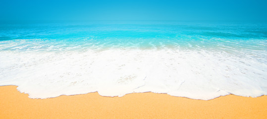Beautiful Tropical  beach with Soft wave of blue ocean, sand and transparent sky. Summer travel holiday background concept. Sea panorama.