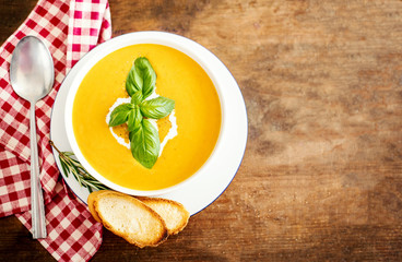 Pumpkin and carrot soup with  croutons on rustic wooden background. Autumn Cream Soup Top view. Copy space..