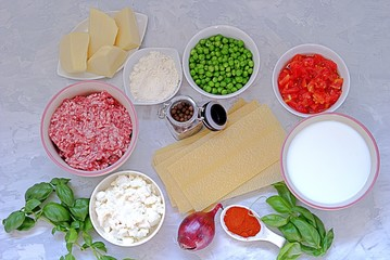 Ingredients for preparation of lasagna with pork forcemeat, green peas and tomatoes.