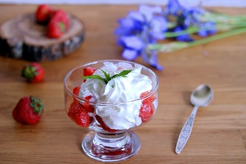 Summer dessert, sliced strawberry with whipped cream in a glass vase. Summer concept