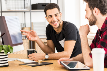 Handsome man showing something on a computer to his colleague in office