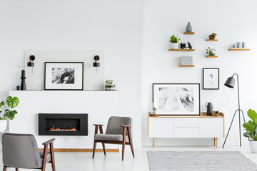 Grey armchairs in white spacious living room interior with posters and fireplace. Real photo