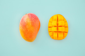 Fresh and beautiful mango fruit with sliced diced mango chunks on a light blue background, copy space(text space), blank for text, top view.