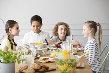 Smiling kids eating dinner while celebrating meeting at home
