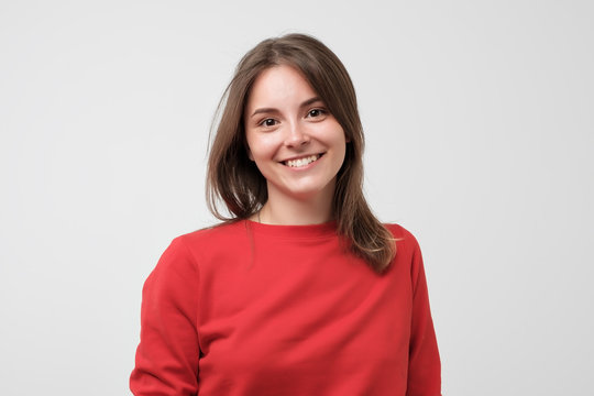 Portrait of young beautiful gcaucasian woman in red t-shirt cheerfuly smiling looking at camera. Studio photo isolated on white background. Copy space.