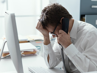 Business executive receiving bad news on the phone