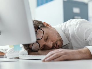 Exhausted business executive sleeping on his desk