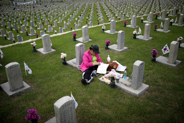 A woman reads a bible in front of the gravestone of a family member who died for the country, on the eve of South Korea's Memorial Day, at the national cemetery in Seoul