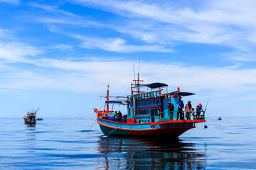 Fishing boat floating in the sea. The beautiful bright blue sky.