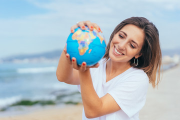 Happy young woman holding a globe