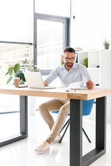 Full length image of caucasian unshaved businessman 30s in white shirt working in office on laptop, and looking at clipboard with paper documents
