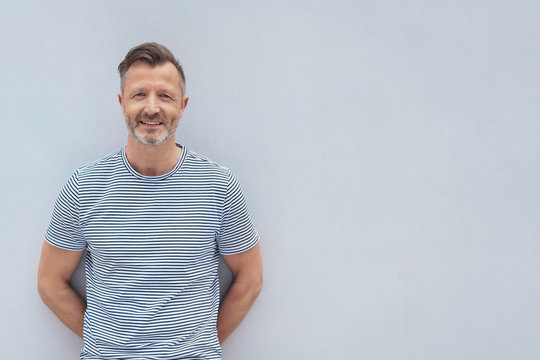 Friendly middle-aged man posing against a wall