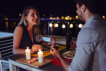 Young beautiful couple having romantic dinner on rooftop