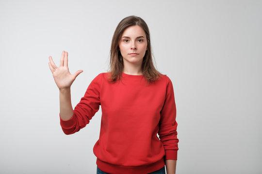 Pretty woman making Vulcan greeting. Concept of great film fan.