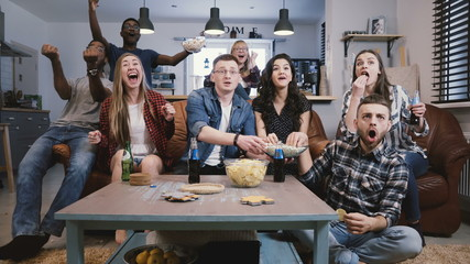 Friends watch sports on TV, cheer and celebrate. Happy diverse supporters fans sit on couch with popcorn and drinks. 4K.