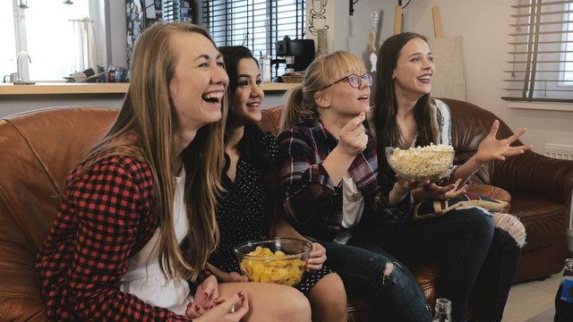 Beautiful girlriends watch soap opera on TV. Girls smile and laugh enjoying emotional romantic movie 4K slow motion.