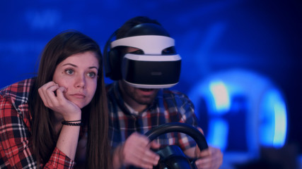 Slightly bored girl watching her excited boyfriend playing racing game in vr headset