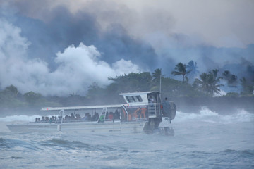 People watch from a tour boat as lava flows into the Pacific Ocean in the Kapoho area, east of Pahoa