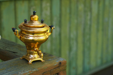 Old traditional Russian samovar on a wooden green wall background.
