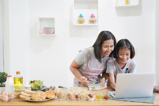 Mother and daughter learn cooking using laptop computer in the kitchen at home, happy family asian concept