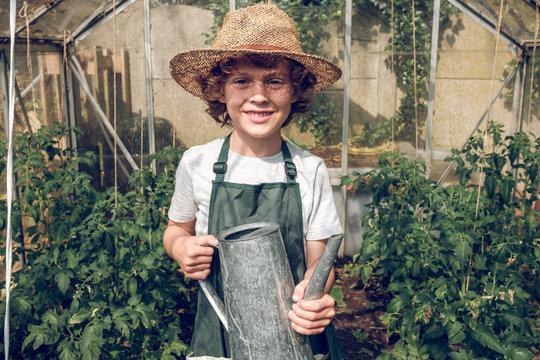 Kid watering plants in greenhouse