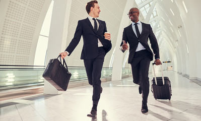 Two businessmen traveling running through airport, smiling looking successful