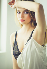 Portrait of beautiful young woman in nightwear on bed