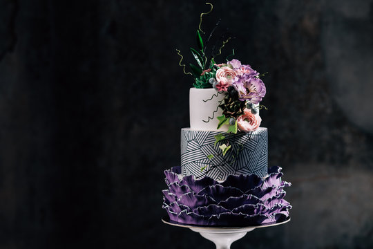 Purple happy birthday cake with beautiful flowers. Dozen of violet cakes with gold and fruits. Exquisite desserts.Tasty white tired cake decorated with violet flowers