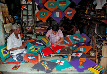 Kite-makers make kites with pictures of the national flags of the countries participating in the upcoming FIFA World Cup in Russia, at a workshop in Kolkata