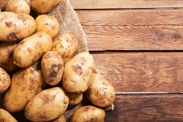 fresh potatoes on a wooden table, top view