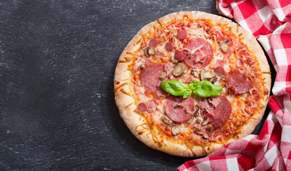 pizza with ham, salami and mushrooms, top view