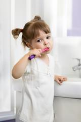 Child toddler girl brushing teeth in bathroom