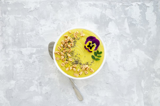 Yellow smoothie bowl with Chia seeds, air wheat and pansy flower on concrete background