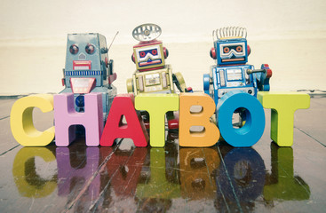 the word  CHAT BOT with wooden letters and retro toy robots  on an old wooden floor