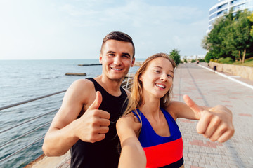 Smiling sportswoman and sportsman in sportswear showing a thumb up while taking a selfie during workout on the quay, near the sea.