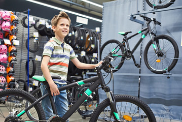 Boy and bicycle in sport shop