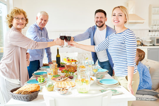 Portrait of happy two generation  family enjoying dinner together clinking glasses over festive table  with delicious dishes and smiling looking at camera, copy space