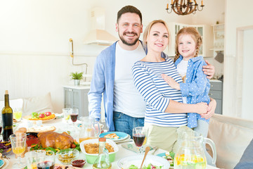 Portrait of happy young family  with cute little girl standing at festive dinner table with delicious dishes and smiling at camera in modern apartment lit by sunlight, copy space