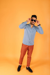 Young business man with glasses looks at the camera on a yellow background.Studio shot of young handsome Indian man wearing sunglasses against yellow background