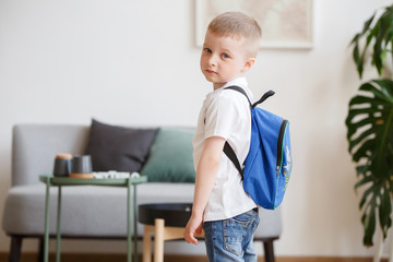 Picture of boy with backpack near sofa