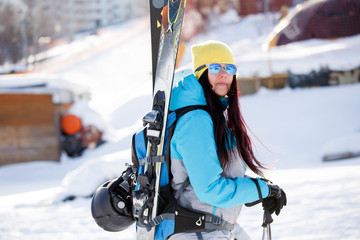 Image of happy sports woman with skis and sticks in winter
