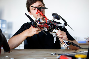Picture of man fixing square copter at table