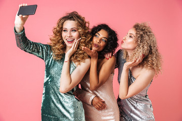 Three beautiful smiling women in shiny dresses